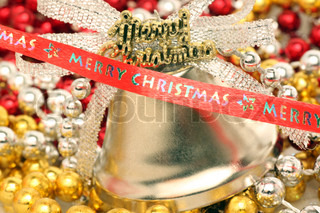 Merry Christmas ribbon in front of bell and beads