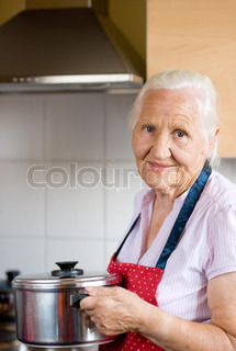 Smiling senior woman in the kitchen is holding a casserole