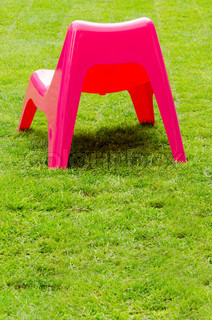 Red plastic chair on green grass