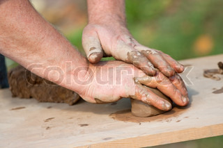 Hands of potter forming wet clay
