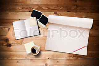 Workspace with coffee cup, instant photos, note paper and notebook on old wooden table