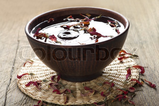 Bowl of water with flower petals and on a straw mat on a vintage wooden table