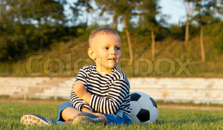 Young boy sitting with his soccer ball