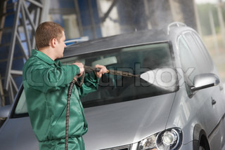worker cleaning car with pressured water
