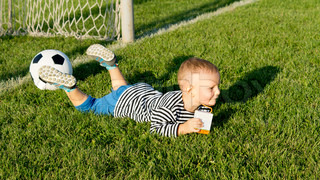 Boy lying in soccer goalposts