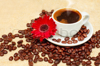 Coffee cup, beans, red flower on linen texture