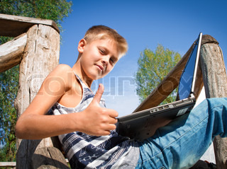 boy with laptop on the nature