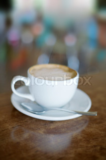 white coffee cup on brown