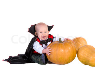 little baby boy in black halloween cloak playing with pumpkins, isolated on white background