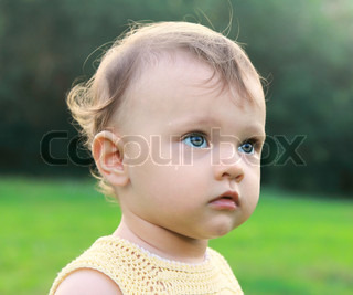 Serious fun baby girl on nature green background thinking looking with interest