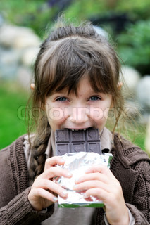 Little cute girl eating chocolate