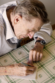 old wrinkled man writing a note on kitchen table