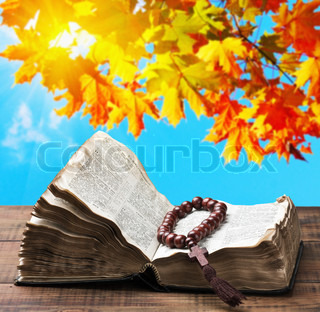 Open Bible and wooden rosary on the background of autumn nature