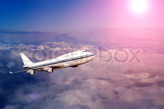 passenger airplane in the clouds at sunset or dawn travel by air transport flying to the top of the airliner nobody