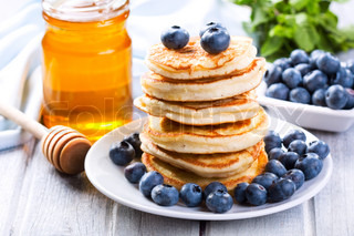 Delicious stack of US pancakes with honey and blueberries