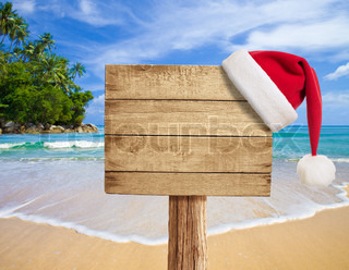 tropical beach wooden signboard with Christmas hat