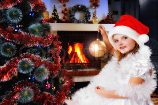 girl in a Santa hat decorating Christmas tree, fireplace on background