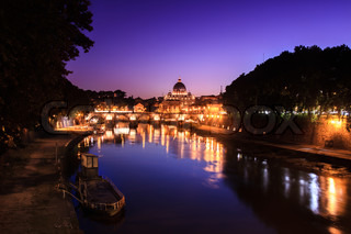Rome, the vatican and a river with reflection in the night with city lights