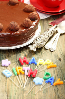 Chocolate cake and candles in the form of letters