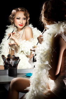 fashionable woman with make-up brush near the mirror