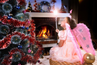 little fairy girl with magic wand near a Christmas tree, fireplace on background