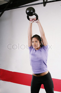 Athletic young woman doing a fitness workout with Kettlebell weights