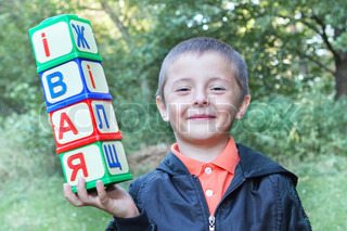 A boy holds a toy cubes with letters outside