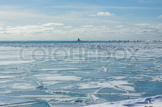 Icy landscape with lighthouse on a pier
