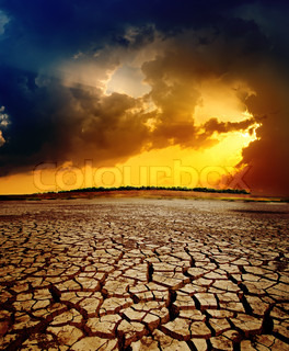 dramatic sunset over dry cracked earth