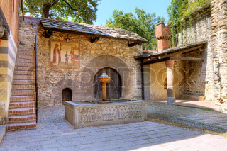 Cobbled courtyard of Valentino Medieval Castle aka Castello del Valentino, small stone house with ancient wooden door and fountain in Turin, Italy.