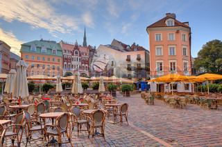 Cobbled city square with outdoor restaurants among colorful buildings in Riga, Latvia