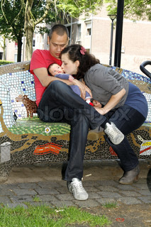 young couple on a bench mother kissing her baby