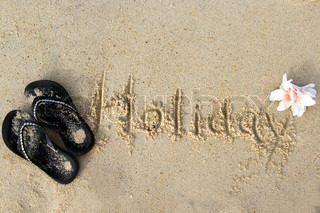 Word Holiday written on the wet sand