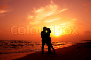 an amorous couple are kissing at sundown