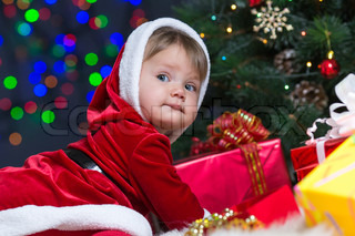 Little girl with plaits is climbing on a tree stock photo