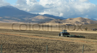 Beautiful mountains and a farmer on a tractor! Vote for me! Photography is my passion!