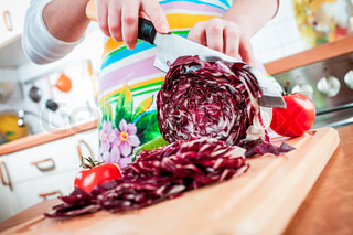 Woman's hands cutting red cabbage