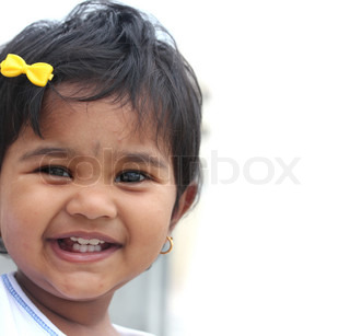 Photo of pretty and happy indian baby girl with expressive eyes and photogenic face expressing toddler's innocence with a beautiful smile The child is of pre school/kinder-garten age
