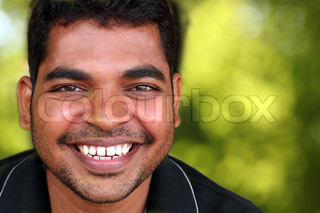Photo of happy lively handsome middle-aged Indian/asian youth laughing and having fun The eyebrows are thick and prominent and hair is black and curly with unshaven stubble on the face
