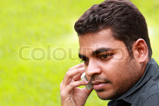 Photo of handsome young indian/south asian businessman talking and listening on cell phone with copy space for text