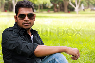 Photo of an handsome, stylish, casual and young indian/south indian youth with sunglasses looking at the camera in a garden with lawn and trees in the background