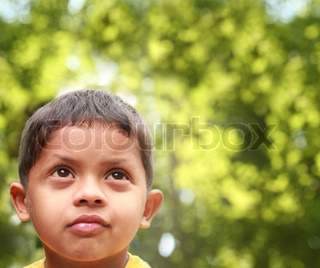 Young indian boy of kinder-garten school age thinking or dreaming about playing and having fun after being bored Background is blurred trees in the backdrop acting as copy-space