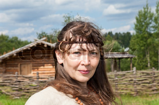 Young women on background of ancient traditional russian village X century