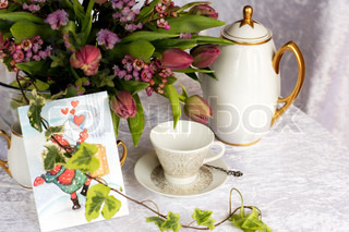 romantic table laid with old coffee cup, pot, flowers and greeting card