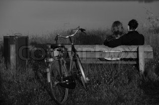 Loving couple, boy and girl, with the bike sitting on the bench in black and white.