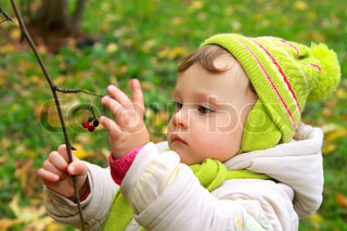 Baby girl holding ash berry in hand and looking on autumn background