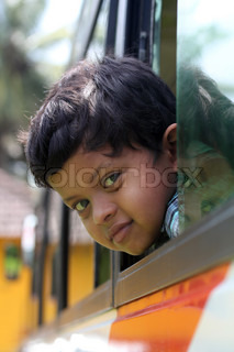 Handsome and cute little indian school kid looking back with happiness from the window of a school bus The face shows the innocence and childishness of the 6 year old boy with a smile on his face