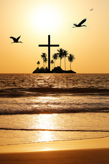 Majestic & heavenly seascape in the evening with island and a cross in the horizon The evening sky is brightly lit by the setting sun with birds flying The water waves are reflecting the sunlight