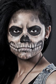 Young woman in day of the dead mask skull Halloween face art