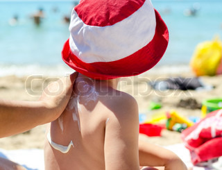 No titleYoung boy sitting on the beach during his summer vacation having sunscreen applied to his back by a parent to prevent burning from harmful UV rays